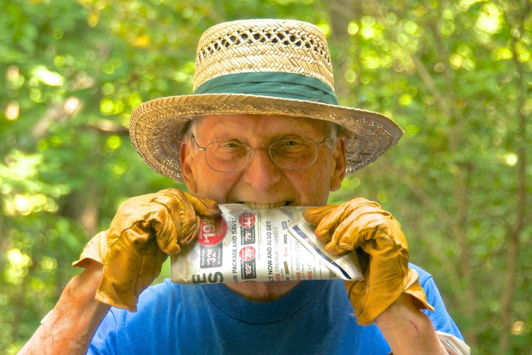 Man holding newspaper in his mouth
